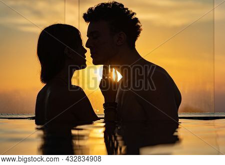 Silhouette Of Loving Couple In The Infinity Pole Water During Sunset. Romance And Relationship