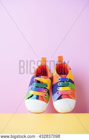 Multi-colored Denim Sports Shoes For Baby, Stands On A Pink And Yellow Background . The Concept Of C