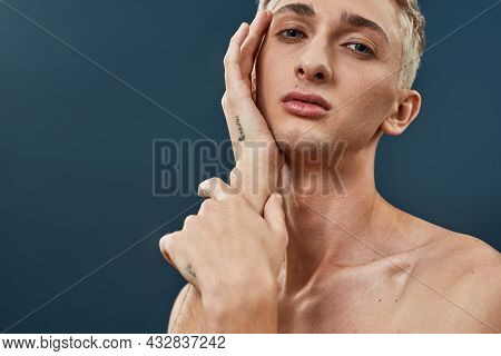 Portrait Of Androgynous Transgender Young Man With Makeup And Light Hair Touching His Face And Looki