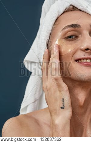 Half Face Closeup Of Happy Young Transgender With Towel Wrap Applying Under Eye Gel Patches Taking C