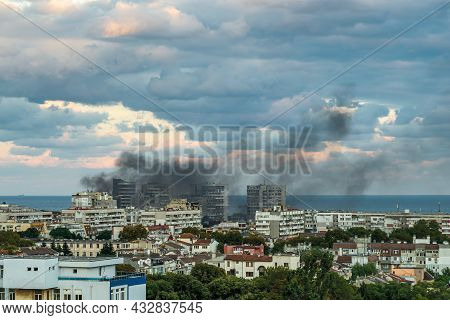 Fire Accident In A Small Seaside Town On A Summer Day. A Multi-storey Residential Building Is On Fir