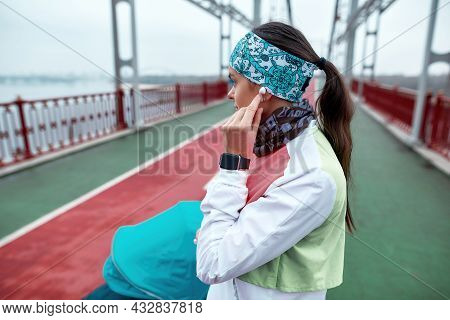 Sportive Woman Using Earbuds While Standing On The Bridge With A Baby Carriage, Ready For A Jog On A
