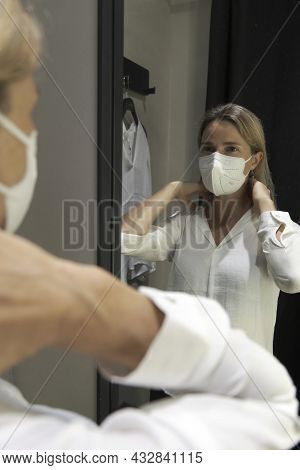Mature Woman With Protective Face Mask, Choosing And, Try On Clothes On The Mirror