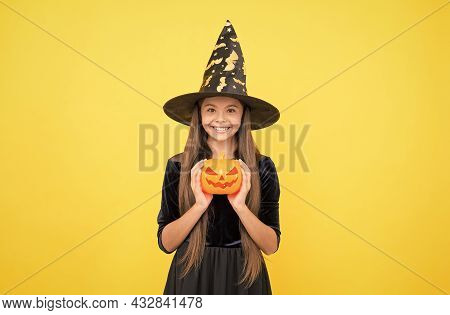 Happy Child Wear Witch Hat Holding Magic Wand And Pumpkin Jack O Lantern To Create Enchantment On Ha
