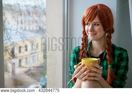 Portrait Of A Red-haired Girl In A Green Shirt Sitting On The Windowsill And Holding A Yellow Tea Mu