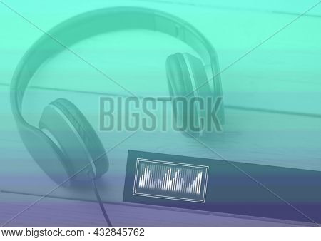 Composition of headphones and eq frequency meter on green and purple streaked background. music communication concept template with copy space digitally generated image.