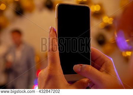 A Phone With A Black Screen In The Hands Of A Young Girl With A Blurry Background. Close-up Photos.