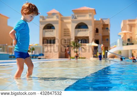 Toddler Boy In Ultraviolet Protective Swimsuit Walking In Shallow Water In The Pool During Summer Va