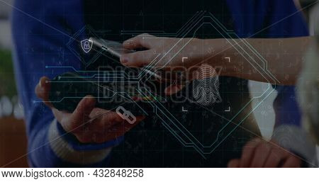 Image of digital interface with fingerprint over two Caucasian people making a payment with smartphone. Global digital network technology security concept digitally generated image.