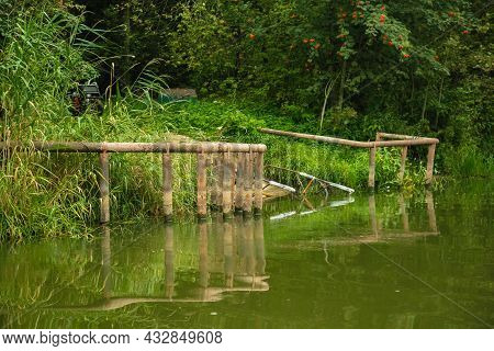 Remains Of An Old Bridge On The River Bank, Summer Forest Landscape.