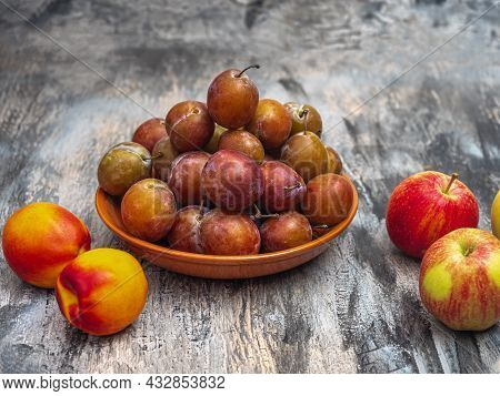 Fresh Fruit For A Light Lunch. Plums On A Clay Plate, Nectarines And Apples On The Table