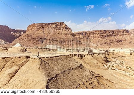 The Judean Desert. Israel. Woman tourist in a red sweater admires the landscape. Interesting walk among picturesque hills, cliffs and limestone gorges. Dead Sea.