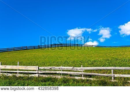 Green grassy pastures fenced in with neat wooden fences. The Dolomites on a sunny autumn day. Europe, Val de Funes. Tyrol, Italy