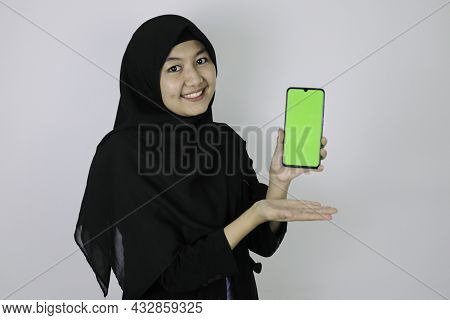 Happy Asian Islamic Business Women Pointing And Show Blank Screen On Phone.