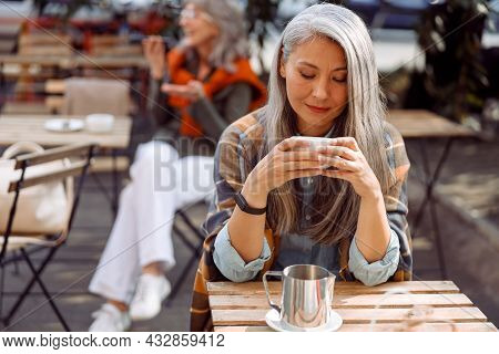 Senior Cafe Guests, Focus On Pretty Silver Haired Lady Holding Cup Of Drink