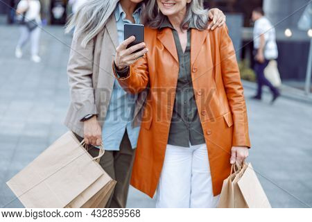 Senior Lady In Leather Jacket And Companion With Shopping Take Selfie On Modern City Street