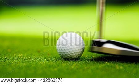Young golfer playing with putter on golf course