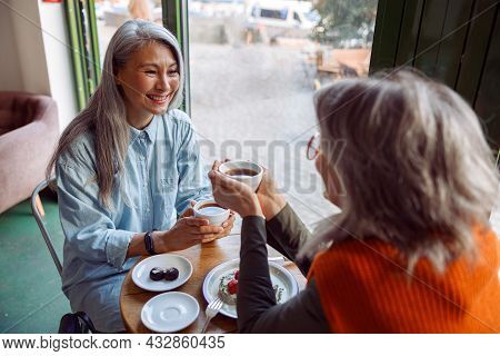 Pretty Happy Mature Women Companions Hold Cups Of Hot Drinks At Small Table In Cozy Cafe