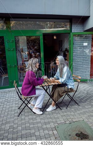 Positive Mature Woman And Grey Haired Asian Companion With Coffee On Outdoors Cafe Terrace