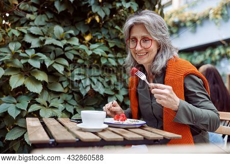 Smiling Mature Female Guest With Glasses Eats Toast At Table On Outdoors Cafe Terrace