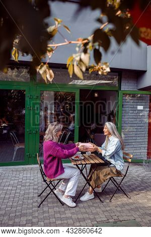 Positive Senior Women Companions Hold Gift Box Sitting Table On Cafe Terrace