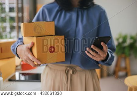 Selective Focus Smartphone On Hand Of Entrepreneur Woman Using And Holding Parcels Shipping Box For