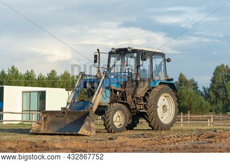 A Blue Tractor Is Leveling A Construction Site For The Installation Of Modular Frame Houses
