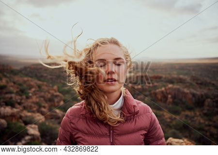 Young Woman With Closed Eyes Feeling Fresh Wind Against Face Standing On Mountain Hill
