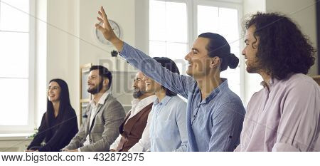 Happy Young Man In The Audience Raises His Hand To Ask A Business Speaker A Question