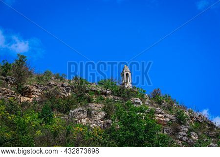 The Tower Of The Winds On A Rocky Hill. A Tall Building On The Top Of A Hill With Large Stones Again