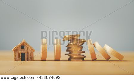 Stack Of Coins Between Falling Wooden Block  And Standing Block To Protect House For Planning And St