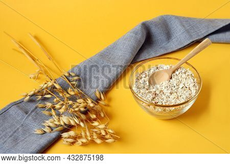The Concept Of Proper Nutrition.a Cup With Oat Flakes, A Wooden Spoon, Oat Branches On A Gray Napkin