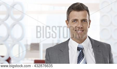 Confident businessman smiling in modern business office. Portrait of mature age, middle age, mid adult man in 40s, happy confident smile. Copy space.