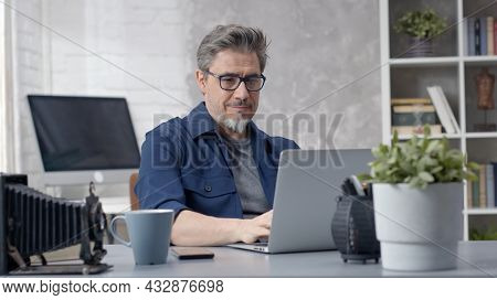 Bearded man working online with laptop computer at home sitting at desk. Businessman in home office, browsing internet. Portrait of mature age, middle age, mid adult man in 50s.