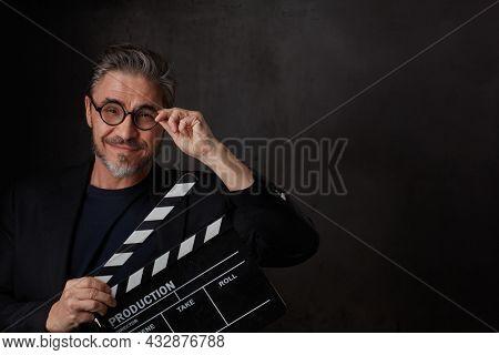 Happy movie director holding black clapper board. Movie director starting film. Copy space, dark background.