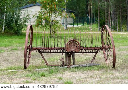 Old Agricultural Machinery With Large Wheels In A Rural Yard