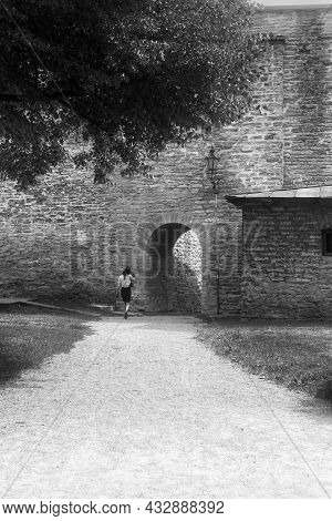 A Young Woman Is Walking Towards The Archway To The Medieval Old Town Of Tallinn, Estonia. She Is De