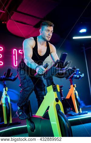 Muscular Active Man In Sportswear Training Cardio With Bicycle. Handsome Strong Man Cycling In Gym.