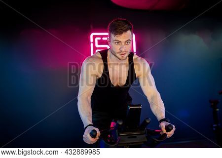 Handsome Strong Man Cycling In Gym. Muscular Active Man In Sportswear Training Cardio With Bicycle.