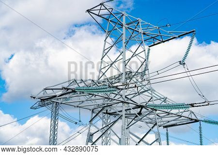 View Of Electric Supply Station. Dark Shadow Of High Voltage Line. High Voltage Pylons Against Blue