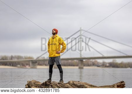Athletic Man Standing On A Fallen Tree Trunk, Relaxing And Taking A Break While Jogging By The River