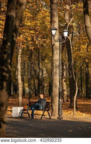 Sad Man Is Sitting On A Bench In An Autumn City Park With A Bouquet Of Flowers And Waits For A Long