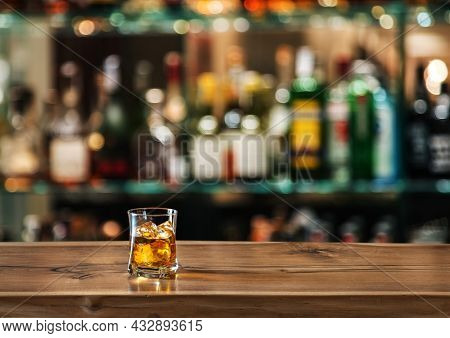 Glass of whiskey on the bar counter. Blurred interior of bar at the background.