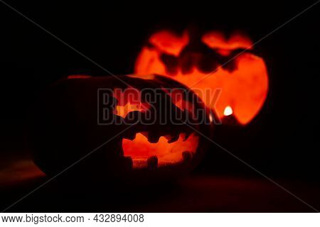 Carved Pumpkin Faces For Halloween. Pumpkins Glow On A Black Background.