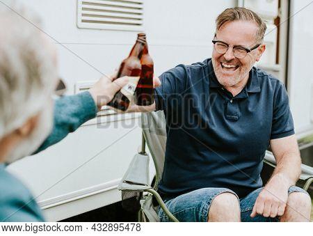 Happy senior men clinking bottle beers