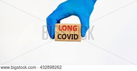 Covid-19 Pandemic Long Covid Symbol. Doctor Hand In Blue Glove Holds Wooden Blocks With Words Long C