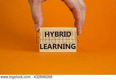 Hybrid Learning Symbol. Concept Words 'hybrid Learning' On Wooden Blocks On A Beautiful Orange Backg