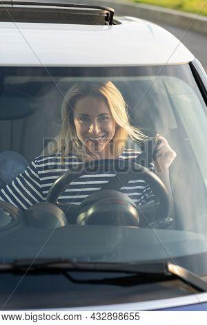Happy Smiling Woman Fastening Safety Seat Belt Sitting On Driver Seat In New Car. Joyful Female Vehi