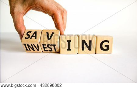 Saving Or Investing Symbol. Businessman Turns Cubes And Changes The Word 'investing' To 'saving'. Be