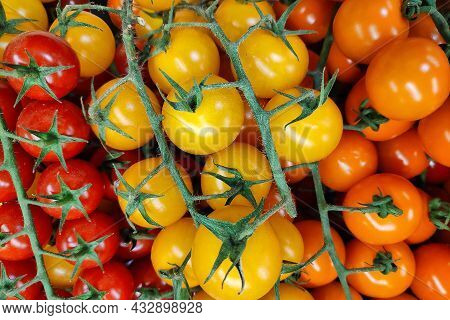 Close-up On A Stack Of Red, Yellow And Orange Cherry Tomatoes Side By Side On A Market Stall.
